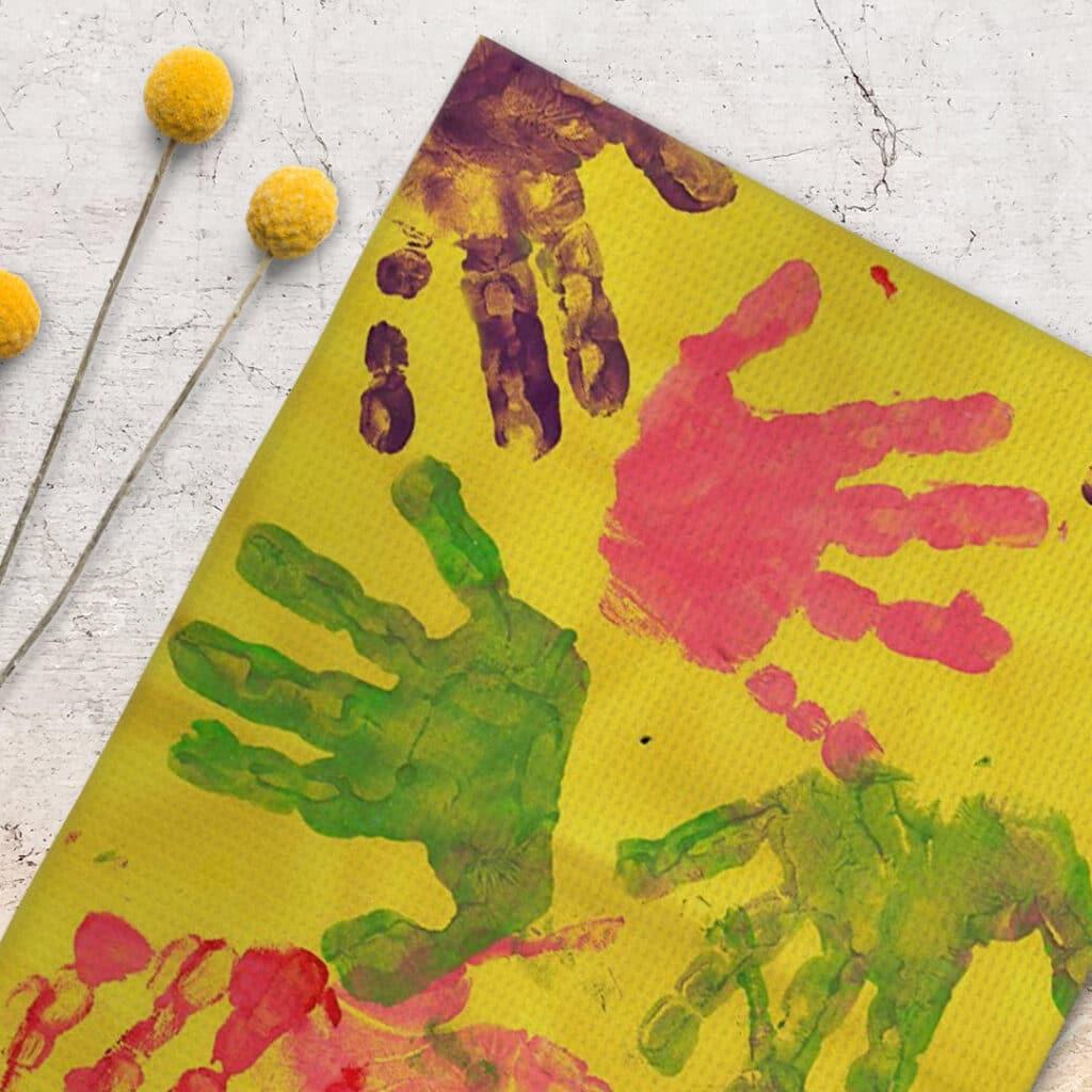 Colorful handprints on a hanging tea towel