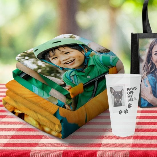 Image of folded photo blanket, pint glass, and tote bag featuring family photos and designs
