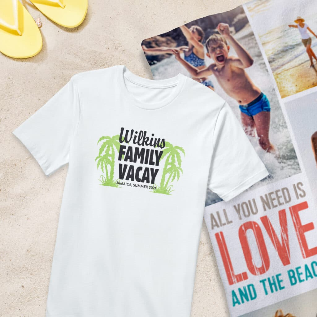 """Flat lay image of a white t-shirt with a """"Wilkins Family Vacay"""" design. Behind the t-shirt lies a personalized beach towel."""