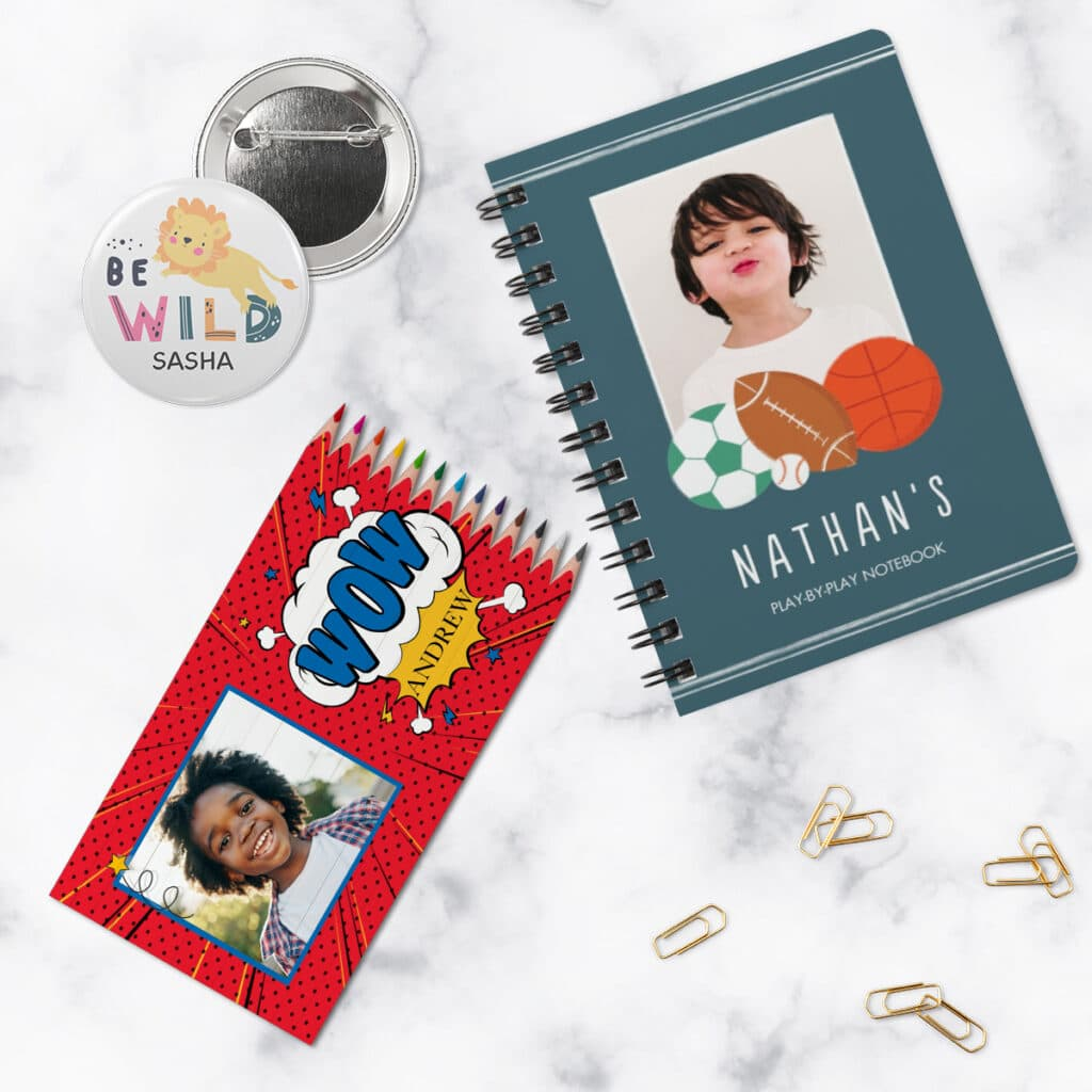 Flat lay image of personalized notebook, colored pencil set, and pin with kid-friendly designs and photos