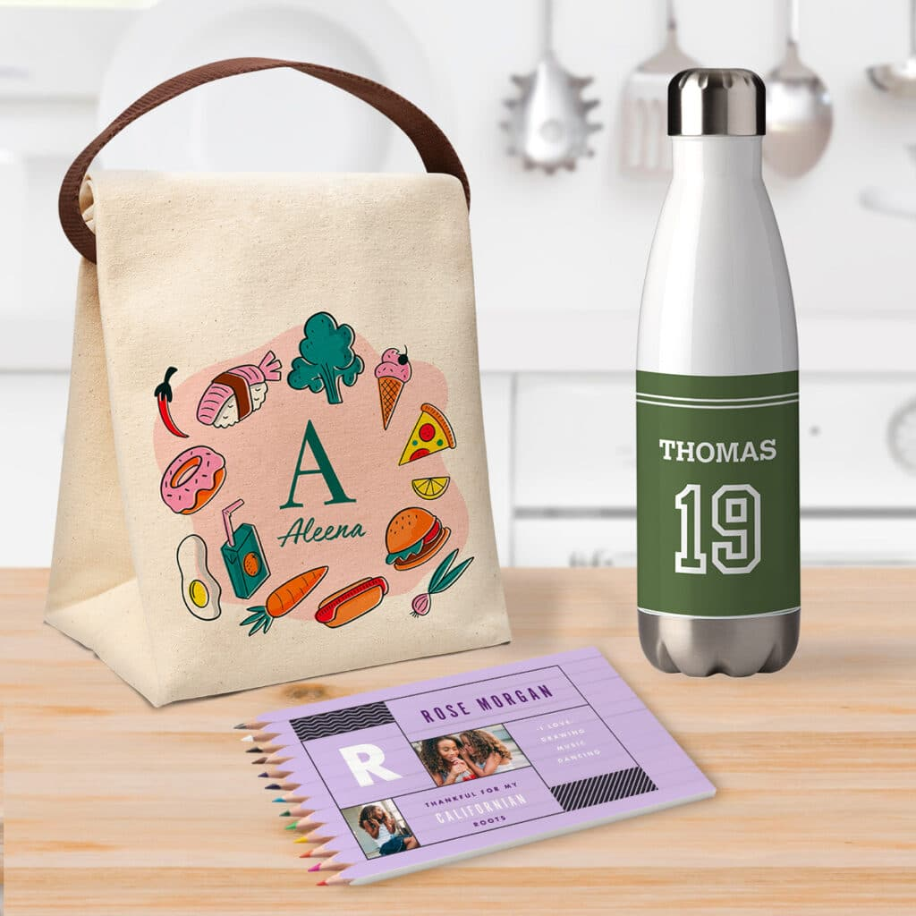 Image of a custom lunch bag, colored pencil set, and water bottle sitting on a kitchen countertop