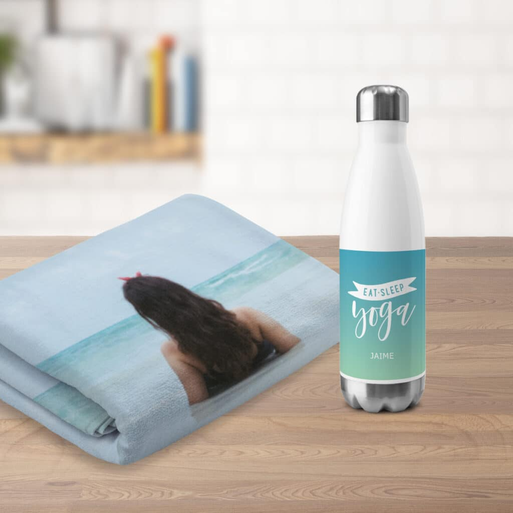 Image of a custom beach towel next to an insulated water bottle on a countertop.