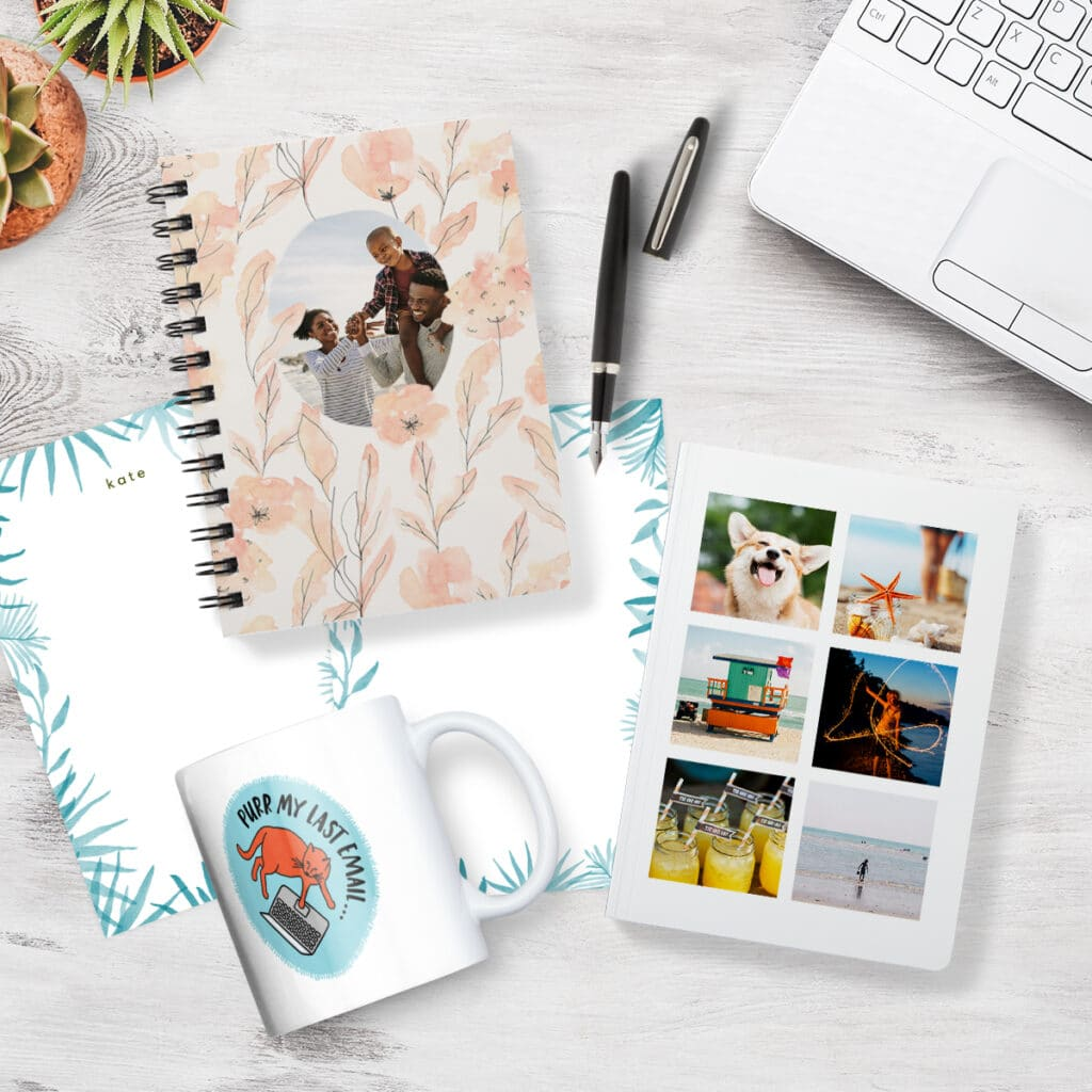 Image of a desktop with personalized stationery, notebooks, and a custom coffee mug. Nearby is a laptop, pen, and houseplants.