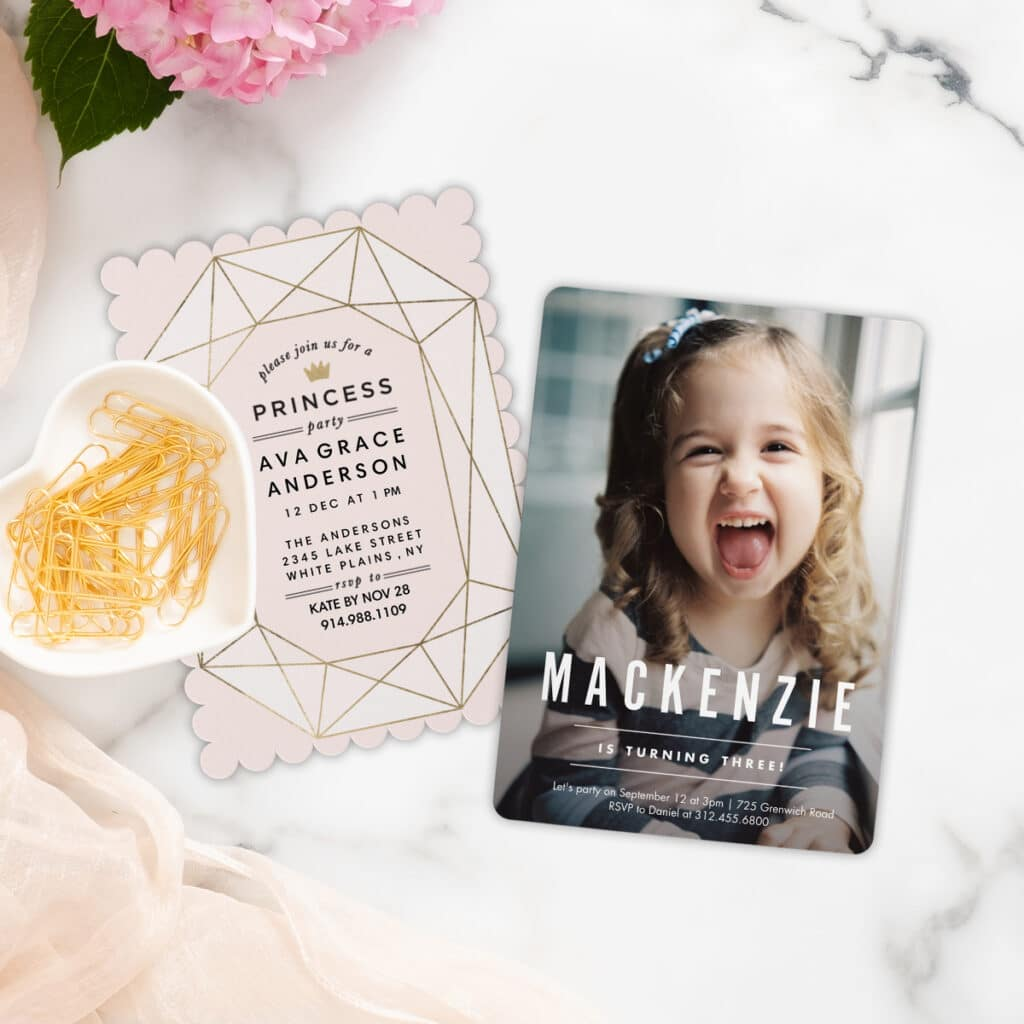 Image of two kids' personalized birthday party invitations. Next to them is a bowl of gold paperclips and pink flowers.