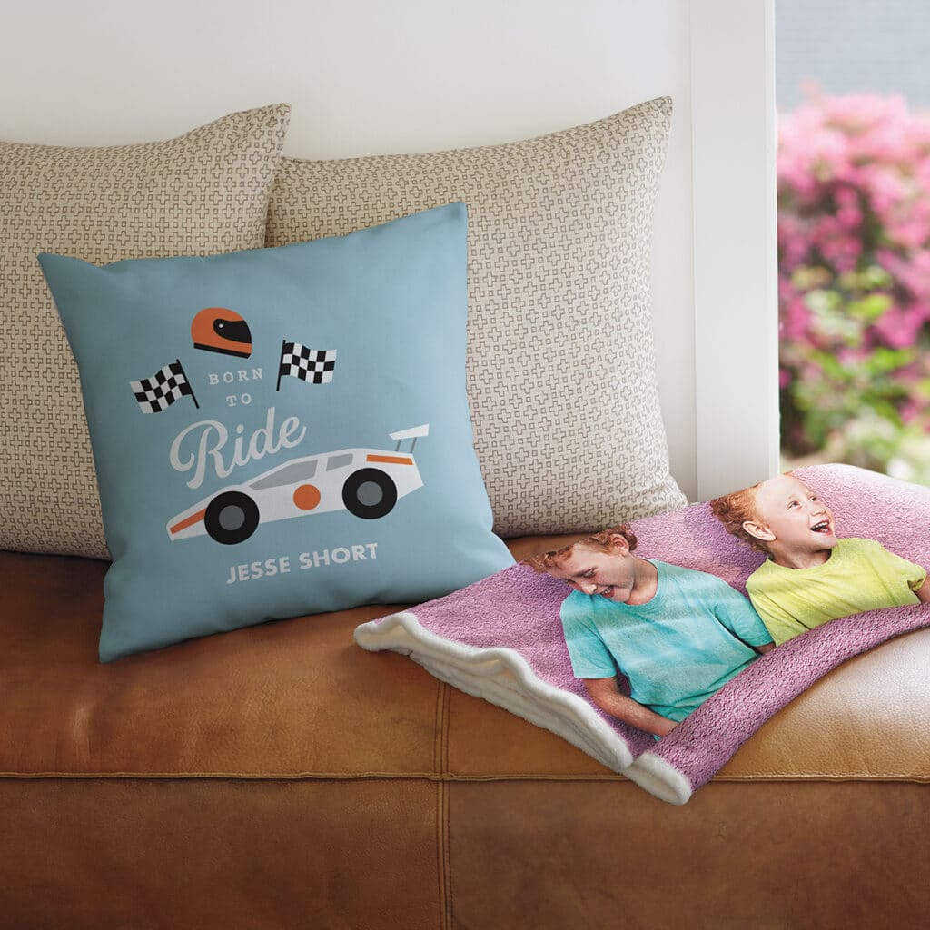 Image of a living room sofa with a photo blanket and personalized pillow .
