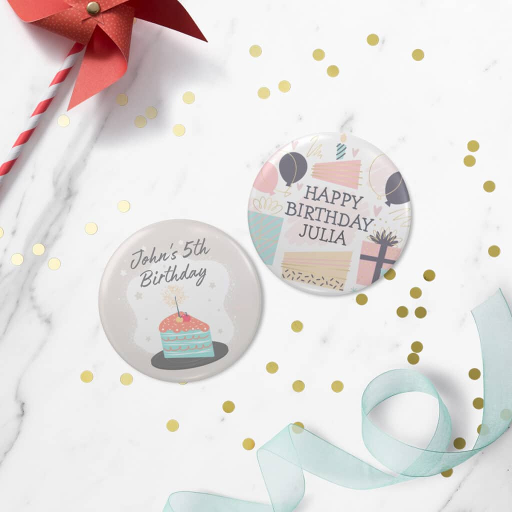Image of two personalized photo buttons with birthday-centric designs. Laying next to them are ribbon, confetti, and a pinwheel.